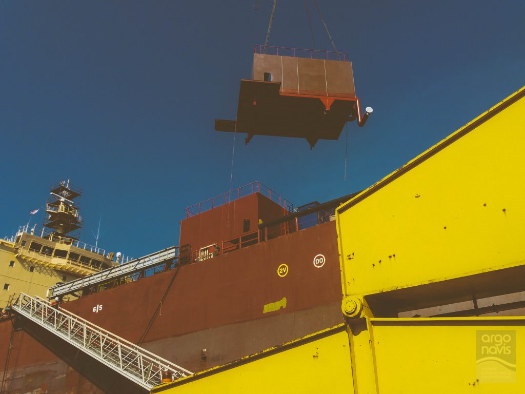 The deckhouse that will house a BWTS system treatment is being lifted by crane on deck.